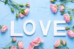 Exprimez l'amour fait à partir des lettres en bois blanches et des fleurs roses de roses Image stock