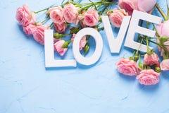 Exprimez l'amour fait à partir des lettres en bois blanches et des fleurs roses de roses Photos libres de droits