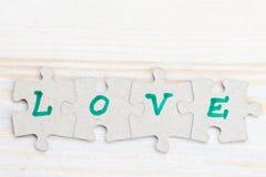 Exprimez l'amour fait de quatre morceaux de puzzle denteux sur t en bois léger Image stock