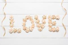 Exprimez l'amour fait de roses blanches avec des rubans sur la table en bois blanche Image libre de droits