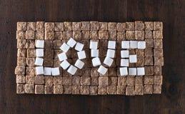 Exprimez l'amour fait de sucres bruns et blancs, vue supérieure Photos stock