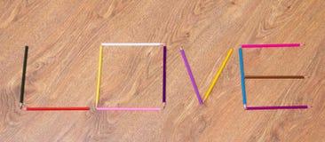 Exprimez l'amour fait par les crayons colorés sur la table photographie stock libre de droits