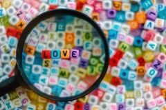Exprimez l'AMOUR sur la loupe avec le fond de perles de lettre d'alphabet Image libre de droits