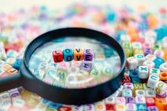 Exprimez l'AMOUR sur la loupe avec le fond de perles de lettre d'alphabet Photos stock