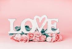 Exprimez l'AMOUR sur le fond de rose en pastel avec le groupe de roses, vue de face Disposition femelle créative de vacances Photographie stock libre de droits