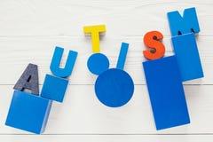 Exprimez l'autisme établi des blocs en bois colorés sur le fond en bois photos stock