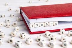 Exprimez l'exode écrit dans les blocs en bois dans le carnet rouge sur l'OE blanc photo libre de droits