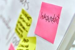 Exprimez l'indépendant écrit sur les autocollants de papier roses et jaunes attachés à un tableau de conférence images stock