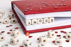Exprimez l'intrigue amoureuse écrite dans les blocs en bois dans un carnet sur le blanc courtisent Photos stock