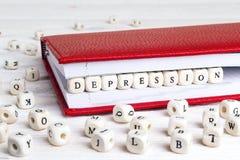 Exprimez la dépression écrite dans les blocs en bois dans le carnet rouge sur le petit morceau photographie stock libre de droits
