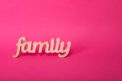 Exprimez la famille, lettres en bois sur le fond de papier rose avec l'espace libre pour le texte Concept d'amour et d'unité Photographie stock
