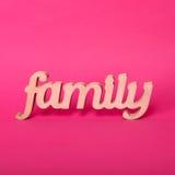 Exprimez la famille, lettres en bois sur le fond de papier rose Concept d'amour et d'unité Images stock