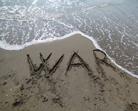 Exprimez la guerre écrite sur le sable de la plage effacée de l'eau photos stock