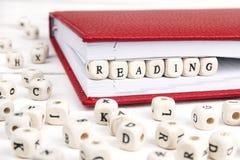 Exprimez la lecture écrite dans les blocs en bois dans le carnet rouge sur W blanc photographie stock libre de droits