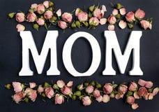 Exprimez la MAMAN avec de petites roses roses sur le fond noir images libres de droits