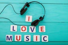 Exprimez la musique d'amour d'I sur le fond en bois bleu avec des écouteurs Vue supérieure Voir les mes autres travaux dans le po Photos libres de droits