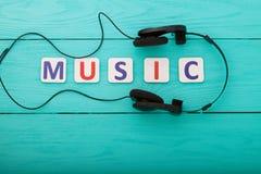 Exprimez la musique sur le fond en bois bleu avec des écouteurs Vue supérieure photos stock