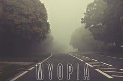 Exprimez la myopie écrite sur la route brumeuse et brouillée, route d'automne de danger Images stock
