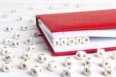 Exprimez la paresse écrite dans les blocs en bois dans le carnet rouge sur le blanc courtisent image libre de droits