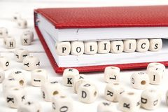 Exprimez la politique écrite dans les blocs en bois dans le carnet rouge sur le blanc photographie stock