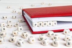 Exprimez la procuration écrite dans les blocs en bois dans le carnet rouge sur le blanc courtisent images stock