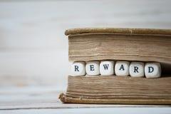 Exprimez la récompense écrite dans les blocs en bois dans le livre photos libres de droits