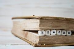 Exprimez la récompense écrite dans les blocs en bois dans le livre image libre de droits