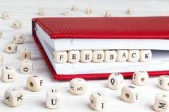 Exprimez la rétroaction écrite dans les blocs en bois dans le carnet rouge sur le blanc image stock