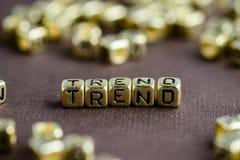 Exprimez la TENDANCE faite à partir de petites lettres d'or sur le backgroun brun photographie stock