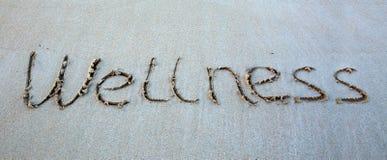 Exprimez le bien-être écrit sur le sable près de la mer photographie stock libre de droits
