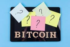 Exprimez le bitcoin dans les lettres et les questions abstraites sur des autocollants collés au comprimé Photo libre de droits