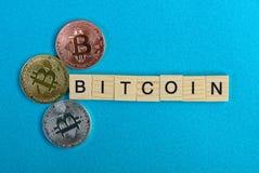 Exprimez le bitcoin des lettres en bois et de trois pièces de monnaie sur un fond bleu photo stock