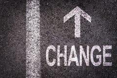 Exprimez le changement et une flèche écrite sur une route goudronnée photo libre de droits