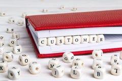 Exprimez le client écrit dans les blocs en bois dans le carnet rouge sur le blanc photographie stock