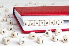 Exprimez le client écrit dans les blocs en bois dans le carnet rouge sur le blanc image libre de droits