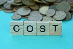 Exprimez le coût de lettres en bois près d'une pile des pièces de monnaie photo stock