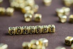 Exprimez le CONCEPT fait à partir de petites lettres d'or sur le backgro brun photographie stock