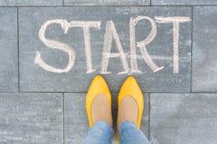 Exprimez le début sur l'asphalte et des pieds de femme photographie stock