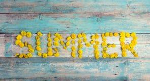 Exprimez le ` d'été de ` des pissenlits jaunes sur le fond en bois de vieille turquoise Image stock