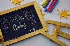 Exprimez le ` de bébé de ` bonjour écrit sur le tableau noir avec la craie colorée images libres de droits