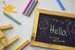 Exprimez le ` de ` bonjour écrit sur le tableau noir avec la craie colorée image stock
