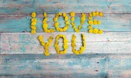 Exprimez le ` de ` je t'aime des pissenlits jaunes sur le fond en bois de vieille turquoise images stock