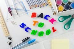 Exprimez le ` de nouveau au ` d'école des lettres en plastique sur un fond blanc avec des articles d'école photos libres de droits