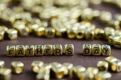 Exprimez le JOUR de PÈRES fait à partir de petites lettres d'or sur le CCB brun image stock