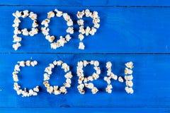 Exprimez le maïs éclaté écrit avec des grains de bruit au-dessus de configuration en bois bleue d'appartement de fond Photo libre de droits