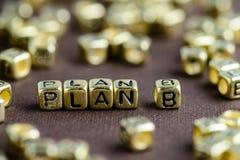 Exprimez le PLAN B fait à partir de petites lettres d'or sur le backgrou brun photographie stock libre de droits