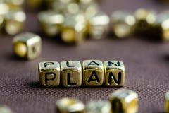 Exprimez le PLAN fait à partir de petites lettres d'or sur le fond brun image libre de droits