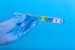 Exprimez le sucre dans la participation de laboratoire une main enfilée de gants photos stock