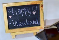 Exprimez le week-end heureux écrit sur un tableau sur lui et le smartphone, ordinateur portable images stock