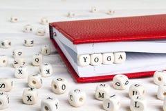 Exprimez le yoga écrit dans les blocs en bois dans le carnet rouge sur le bois blanc photo stock